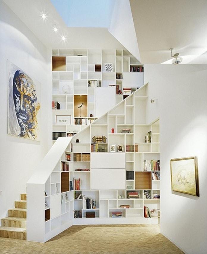 Kiến trúc sư tận dụng phần tay vịn cầu thang để làm tủ trưng bày, vừa làm bàn trà và tủ sách